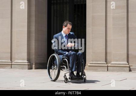 Homme paraplégique en fauteuil roulant contrôle watch Banque D'Images