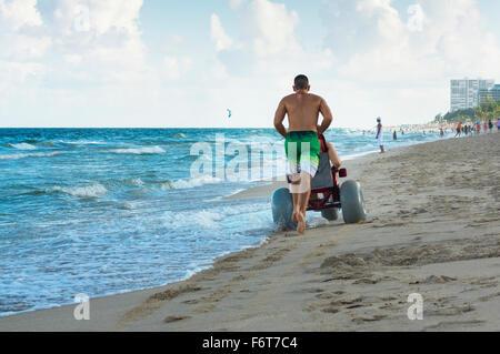 Man pushing paraplégiques en fauteuil roulant en petite amie sur la plage Banque D'Images