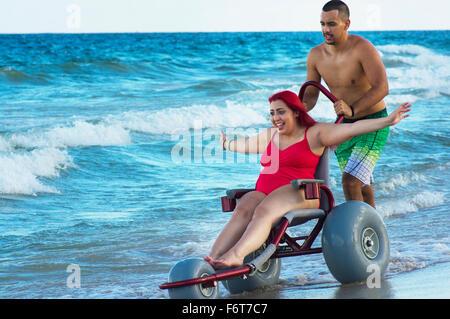 Man pushing paraplégiques en fauteuil roulant en petite amie sur la plage