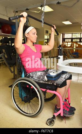 Femme paraplégique en fauteuil roulant l'élaboration dans la thérapie physique Banque D'Images
