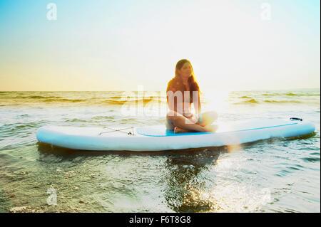 Femme assise sur le lac en paddleboard Banque D'Images