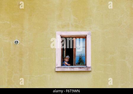 Little Boy à la fenêtre de sortie de très vieille maison. Banque D'Images