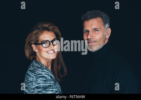Portrait of smiling couple in front of black background Banque D'Images