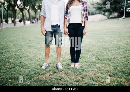 Jeune couple dans l'amour debout sur une prairie dans un parc holding hands Banque D'Images