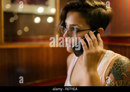 Jeune femme tatouée assis dans un coffee shop talking on phone Banque D'Images