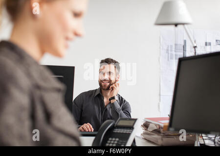 Man in office looking at woman Banque D'Images