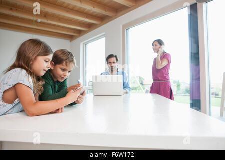 Frère et soeur, parents using laptop in background Banque D'Images
