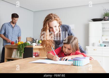 Petite fille fait ses devoirs à la table de la cuisine avec ses parents dans l'arrière-plan Banque D'Images