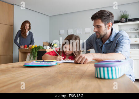 Petite fille fait ses devoirs à la table de la cuisine pendant que son père la regarder Banque D'Images
