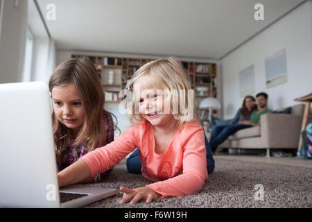 Deux petites sœurs se trouvant sur le plancher au salon avec ordinateur portable pendant que ses parents assis dans Banque D'Images