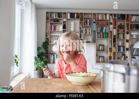 Portrait of laughing little girl eating spaghetti Banque D'Images