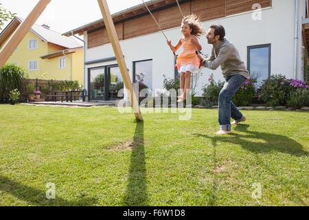 Père fille poussant sur une balançoire dans le jardin Banque D'Images