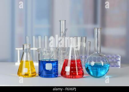 Tables de laboratoire avec verrerie avec des liquides de différentes couleurs Banque D'Images