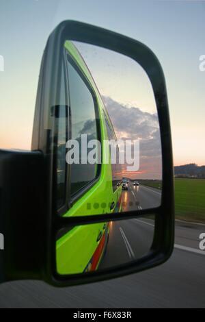 Le trafic routier, les phares et le coucher du soleil dans un rétroviseur d'un véhicule d'urgence Banque D'Images