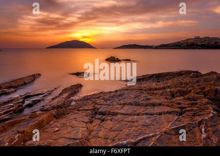 Seascape contre un coucher de soleil spectaculaire et coloré avec des nuages de rêve passant sur la baie mirroring Banque D'Images