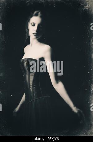 Portrait rétro spectaculaire d'une belle fille gothique triste parmi l'obscurité. L'effet vieux film, noir et blanc Banque D'Images