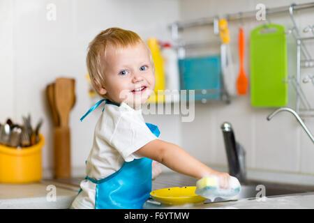 Tout-petit enfant lave-vaisselle dans la cuisine. Petit garçon s'amusant avec l'aide de sa mère aux tâches ménagères. Banque D'Images