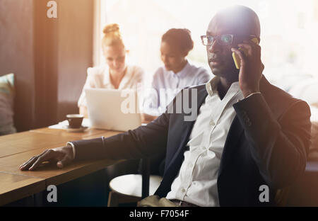 Black business man using cell phone, blanc et noir business woman in background Banque D'Images