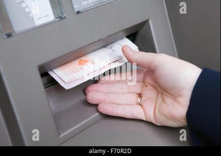 Woman withdrawing cash de l'ATM,