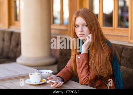 Belle jeune femme rousse aux cheveux longs en blouson de cuir à l'aide de téléphone cellulaire et d'attendre que Banque D'Images
