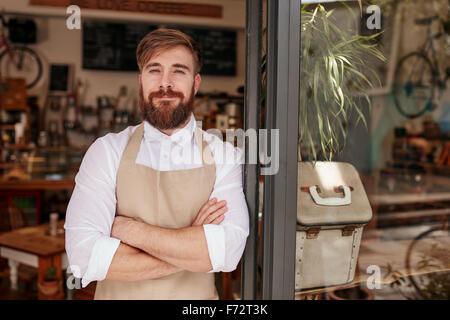 Portrait of a handsome et confiant cafe propriétaire debout à la porte. Jeune homme debout avec les bras croisés looking at camera