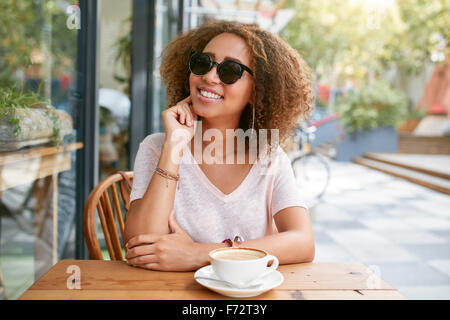 Portrait of cute young girl sitting at outdoor cafe looking at camera et souriant. Jeune femme africaine at sidewalk Banque D'Images