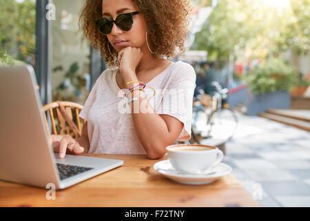 Piscine shot of young African woman at sidewalk cafe la lecture de courriers électroniques sur son ordinateur portable. Banque D'Images