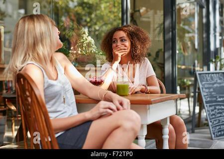 Deux jeunes filles bavardant et riant tout en café-terrasse. Amis féminins partager quelques moments drôles au café Banque D'Images