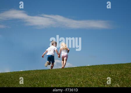 Deux enfants courir vers le haut d'une colline Banque D'Images