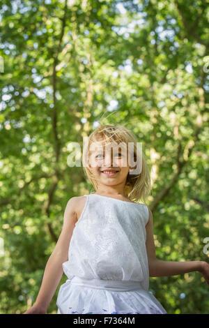 Jeune fille jouant dans une forêt. Banque D'Images