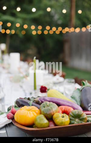 Longue table avec des assiettes et des verres, de l'alimentation et des boissons dans un jardin, un bol de légumes Banque D'Images