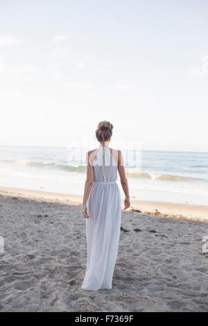 Blonde femme portant une robe longue debout sur une plage de sable. Banque D'Images