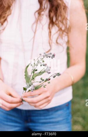 Portrait d'une femme tenant une fleur sauvage.
