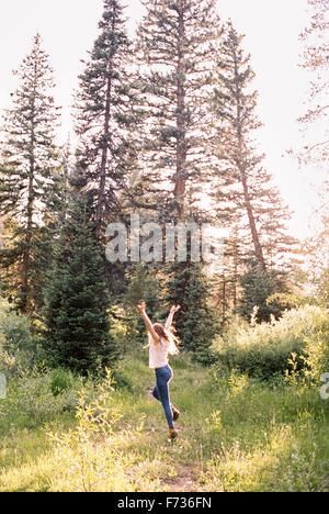 Femme sautant de joie dans une forêt ensoleillée. Banque D'Images