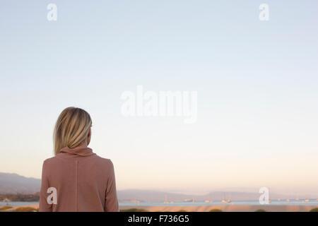 Femme blonde debout à l'océan. Banque D'Images