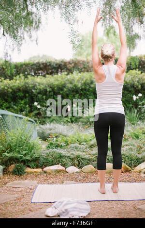 Blonde woman doing yoga dans un jardin. Banque D'Images