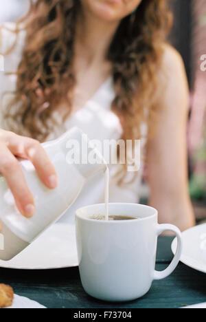 Woman pouring lait dans une tasse de thé. Banque D'Images