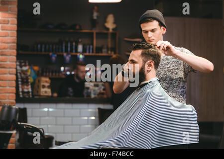 Jeune beau salon de coiffure de décisions de coupe homme barbu attrayant dans ce type de Banque D'Images