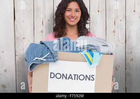 Image composite de volunteer holding clothes donation box