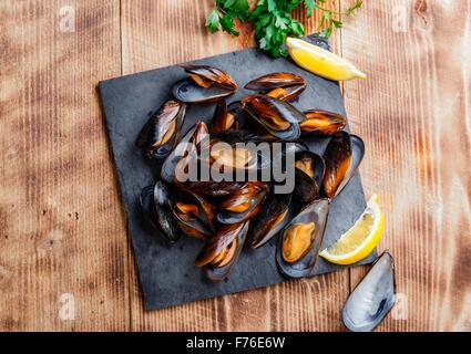 Les moules cuites huîtres au citron et herbes Banque D'Images