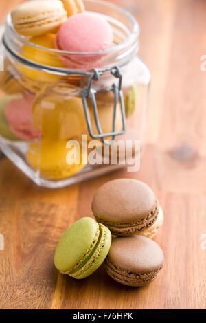 Délicieux macarons colorés dans le bocal sur la table en bois Banque D'Images