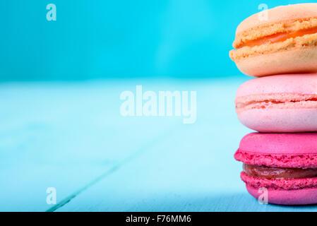 Macarons Français colorés sur fond bleu Banque D'Images