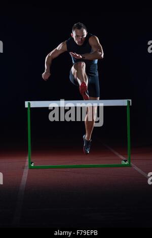 L'homme sportif sautant au dessus des obstacles sur une piste de course d'athlétisme Banque D'Images