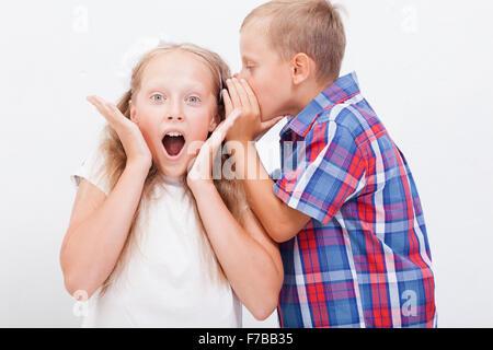 Teenage boy chuchoter dans l'oreille un secret de fille de l'adolescence sur fond blanc Banque D'Images