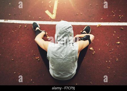 Vue arrière de jeune femme dans les vêtements de sport assis sur la voie et préparer le terrain avant l'entraînement.méconnaissable Banque D'Images