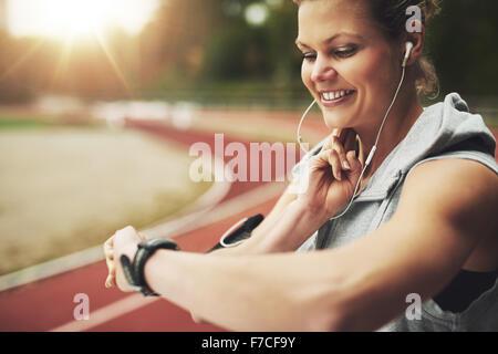 Close-up smiling sportswoman regardant sa montre et se sentir l'impulsion sur la voie avant la formation sur le Banque D'Images