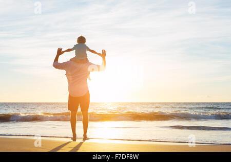 Heureux Père et Fils s'amusant à jouer sur la plage au coucher du soleil. La paternité du concept de famille Banque D'Images