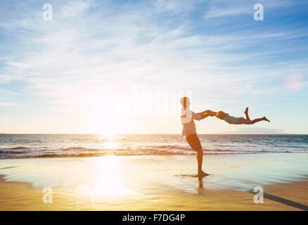 Joyeux Heureux père et fils jouant sur la plage au coucher du soleil. La paternité du concept de famille Banque D'Images