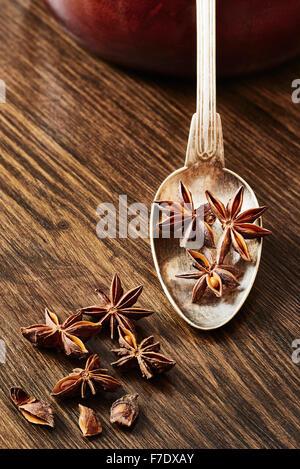 L'anis étoilé sur vieux spoon entouré d'étoiles d'anis sur table en bois sombre. Banque D'Images