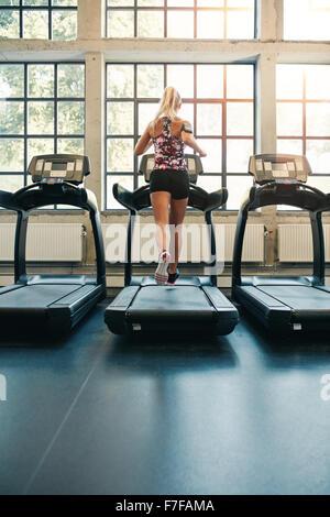 Vue arrière de jeunes femmes s'exécutant sur tapis roulant dans une salle de sport. Jogging femme de remise en forme Banque D'Images